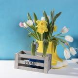 Les bottes en caoutchouc jaunes avec un bouquet des fleurs des jonquilles jaunes et des tulipes blanches et roses Accessoires de  Photos stock