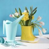 Les bottes en caoutchouc jaunes avec un bouquet des fleurs des jonquilles jaunes et des tulipes blanches et roses sur la table en Photographie stock libre de droits