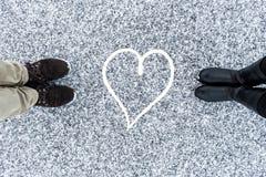 Les bottes masculines et femelles se tenant au symbole de coeur sur l'asphalte ont couvert la surface graveleuse de neige Neigeux Image libre de droits