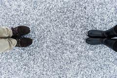 Les bottes masculines et femelles se tenant sur l'asphalte ont couvert la surface graveleuse de neige Neigeux rugueux Textplace L Photo libre de droits
