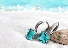 Les boucles d'oreille de bijoux avec l'aigue-marine sur le sable échouent le fond, doux image stock