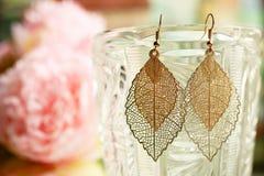 Les boucles d'oreille d'or de dames part étroitement sur le fond coloré brouillé avec des fleurs photographie stock