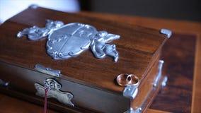 Les boucles de mariage et ont monté Bijoux et anneaux sur la boîte en bois Photo libre de droits