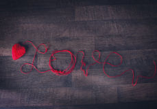Les boucles rouges dans la forme du coeur et du texte aiment Images libres de droits