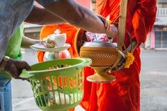 Les bouddhistes ont la foi dans le bouddhisme donnant l'aumône aux moines reçoit a photos libres de droits