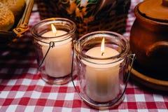 Les bougies brûlantes blanches en verre sur blanc-rouge à carreaux vêtent photo stock