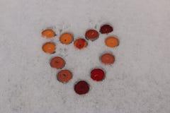 Les bougies brûlantes multicolores lumineuses ont rayé sous forme de coeur dans la neige Photo stock
