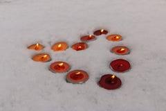Les bougies brûlantes multicolores lumineuses ont rayé sous forme de coeur dans la neige Photos stock