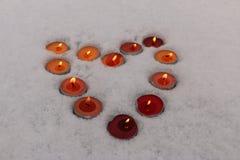 Les bougies brûlantes multicolores lumineuses ont rayé sous forme de coeur dans la neige Photo libre de droits