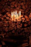 Les bougies brûlent la nuit avec la lumière jaune à l'intérieur dans la perspective du bois de chauffage photo stock