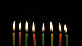 Les bougies brûlantes colorées de longueur ont placé sur le fond noir 4K clips vidéos