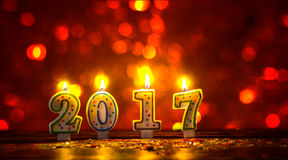 Les bougies brûlantes numéro 2017 et coloré arrose avec le bokeh dedans Photos libres de droits