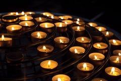 Les bougies brûlent dans l'intérieur foncé de la cathédrale catholique Images libres de droits