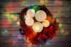 Les bougies décorées des fleurs nichent le panier sur la planche en bois Photographie stock