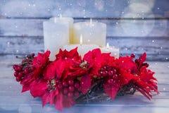 Les bougies décorées des fleurs nichent le panier sur la planche en bois Photo libre de droits
