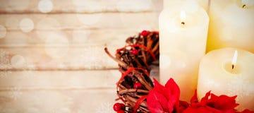 Les bougies décorées des fleurs nichent le panier sur la planche en bois Image stock