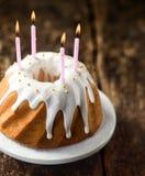 Les bougies d'anniversaire sur un anneau tournoyé de vanille durcissent Photos stock