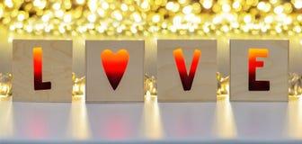 Les bougies dans les boîtes en bois avec des lettres d'AMOUR ont formé des trous Photos stock