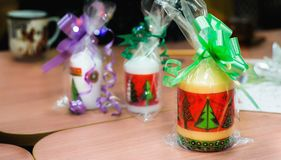 Les bougies de Noël ont emballé avec les rubans colorés sur une table Photographie stock libre de droits