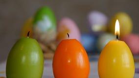 Les bougies ont fait dans la forme de l'oeuf de pâques Bougies éteintes de l'air vert, orange, jaune Bougies d'oeufs de pâques et banque de vidéos