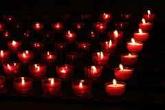Les bougies rouges avec rougeoyer s'allume dans l'obscurité dans l'église Fond de paix et d'espoir Concept de religion Images stock