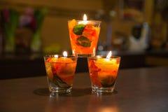 Les bougies s'allument et les feuilles roses à l'intérieur dans le bol en verre Image stock