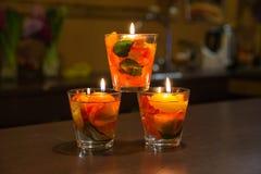 Les bougies s'allument et les feuilles roses à l'intérieur dans le bol en verre Photo stock