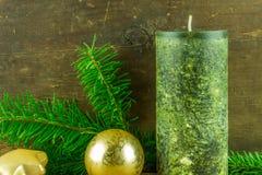 Les bougies vertes avec des boules de Noël et le sapin s'embranchent sur un conseil rustique Images libres de droits