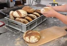 Les boulangers faisant les miches de pain faites main dans une boulangerie de famille formant la pâte dans le tradional forme à S Images stock