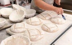 Les boulangers faisant les miches de pain faites main dans une boulangerie de famille formant la pâte dans le tradional forme à S Image libre de droits