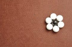 Les boules blanches et noires ont emballé sous forme de fleur Images stock