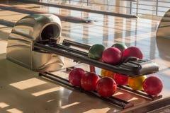 Les boules de bowling sur la boule renvoient le dispositif dans le bowling Image libre de droits