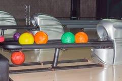 Les boules de bowling sur la boule renvoient le dispositif dans le bowling Photographie stock libre de droits