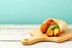 Les boules de Falafel ont servi avec du pain pita et la laitue sur un conseil en bois photo libre de droits