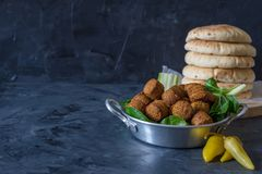 Les boules de Falafel ont servi dans le plat avec les feuilles et le pain pita verts photo stock