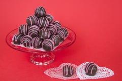 Les boules de gâteau de chocolat ont dépouillé les fontes roses de sucrerie empilées du plat Photos libres de droits