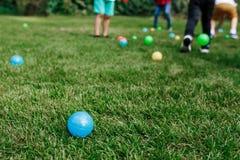 Les boules en plastique colorées de jouet du ` s d'enfants se sont renversées dans l'herbe Activité de fête d'anniversaire de béb image stock