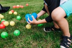 Les boules en plastique colorées de jouet se sont renversées dans l'herbe Garçon gethering les boules bleues Activité de fête d'a photos libres de droits