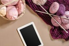 Les boules roses et pourpres de la laine filète avec des aiguilles de tricotage se situant dans le panier sur le fond beige Moque Image libre de droits