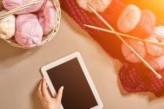 Les boules roses et pourpres de la laine filète avec des aiguilles de tricotage se situant dans le panier sur le fond beige Moque Photos stock