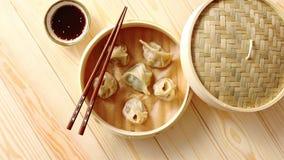 Les boulettes de chinois traditionnel ont servi dans le vapeur en bambou en bois banque de vidéos