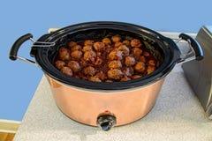 Les boulettes de viande dans le pot inoxydable de cruche ralentissent le cuiseur sur le compteur images libres de droits