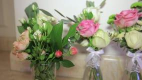Les bouquets avec les fleurs fraîches sont dans des vases en verre As banque de vidéos