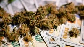 Les bourgeons de marijuana se trouvent sur l'argent images stock