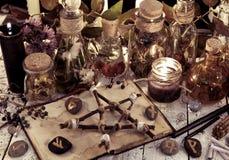 Les bouteilles de breuvage magique, le pentagone étoilé en bois, les bougies noires et les objets magiques sur la sorcière ajourn images stock