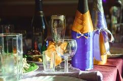 Les bouteilles de champagne et les verres de vin décorés se tiennent sur une table servie par banquet photos stock