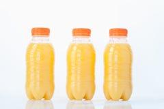 Les bouteilles de jus d'orange sur le fond blanc, se ferment  Photos stock
