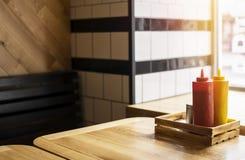 Les bouteilles de ketchup et de moutarde sont sur la fin de table  Photos stock