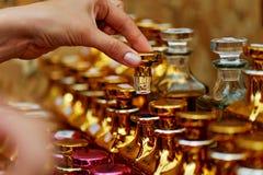 Les bouteilles de parfum en verre ont basé des huiles Un bazar, marché Macro Or et gamma rose Image libre de droits