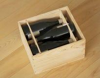 Les bouteilles de vin rouge ont emballé dans la boîte en bois ouverte se tenant sur le plancher en bois image stock